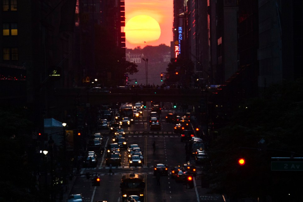"People make their way through 42nd street at sunset, during the ""Manhattanhenge"" in New York City"